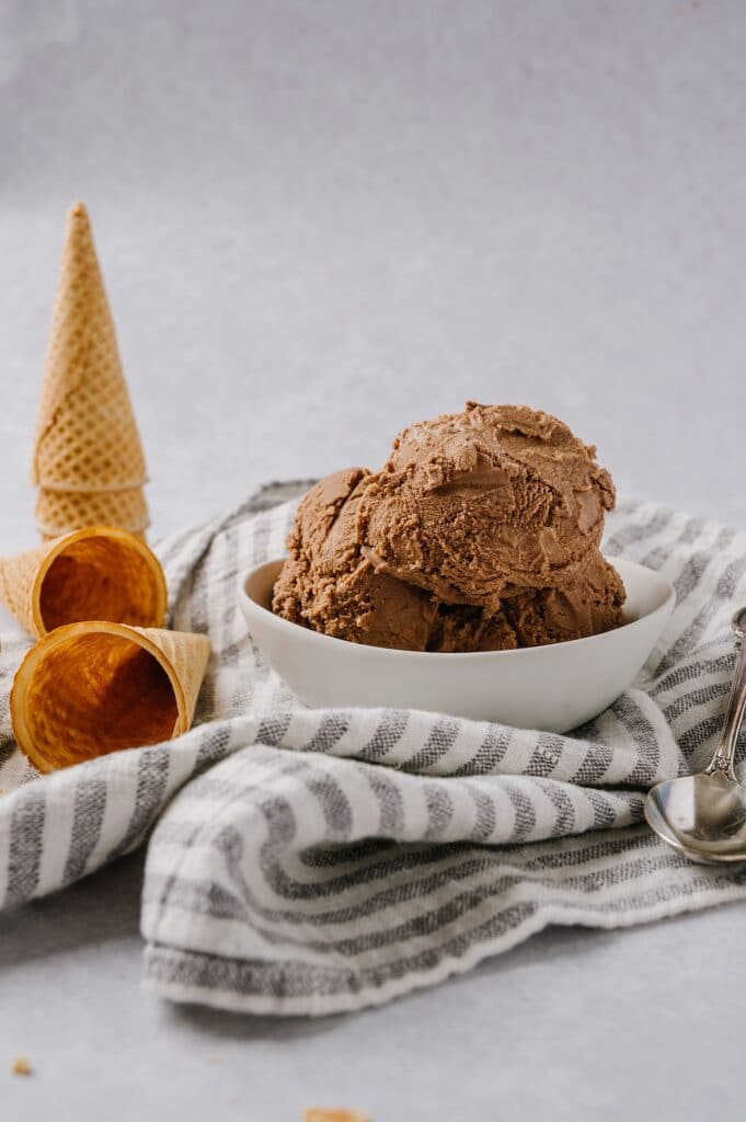 scoops of chocolate ice cream in a bowl with waffle cones in the background