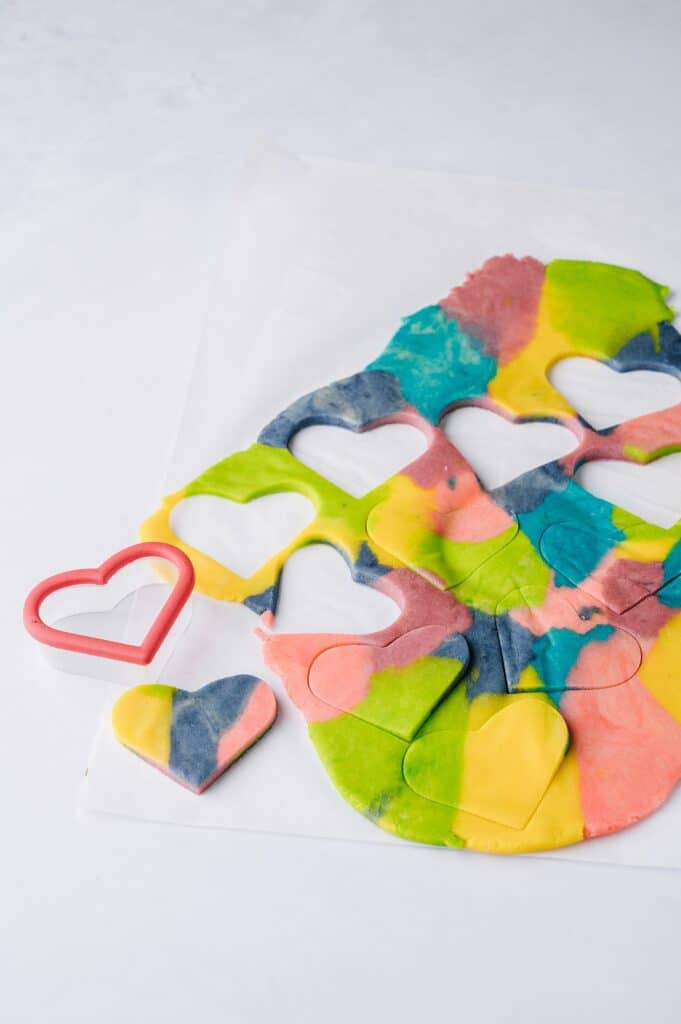 colored sugar cookie dough being cut out with a heart shaped cutter