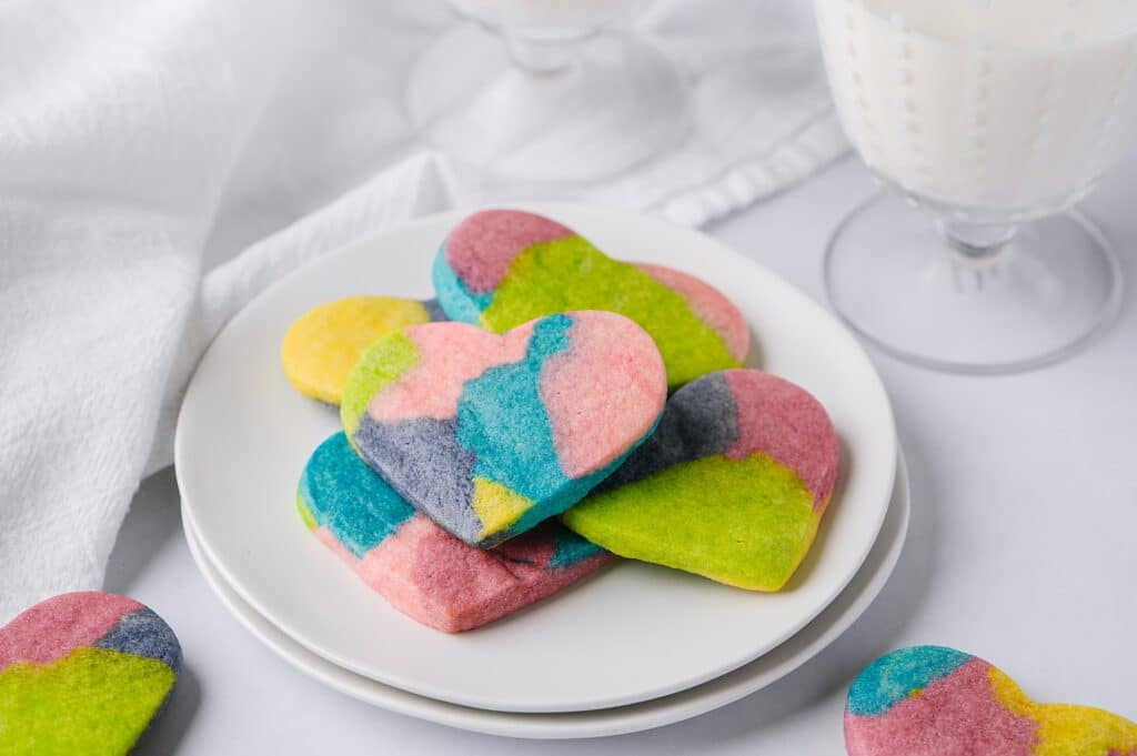 tie dye cookies on a plate with glasses of milk in the background