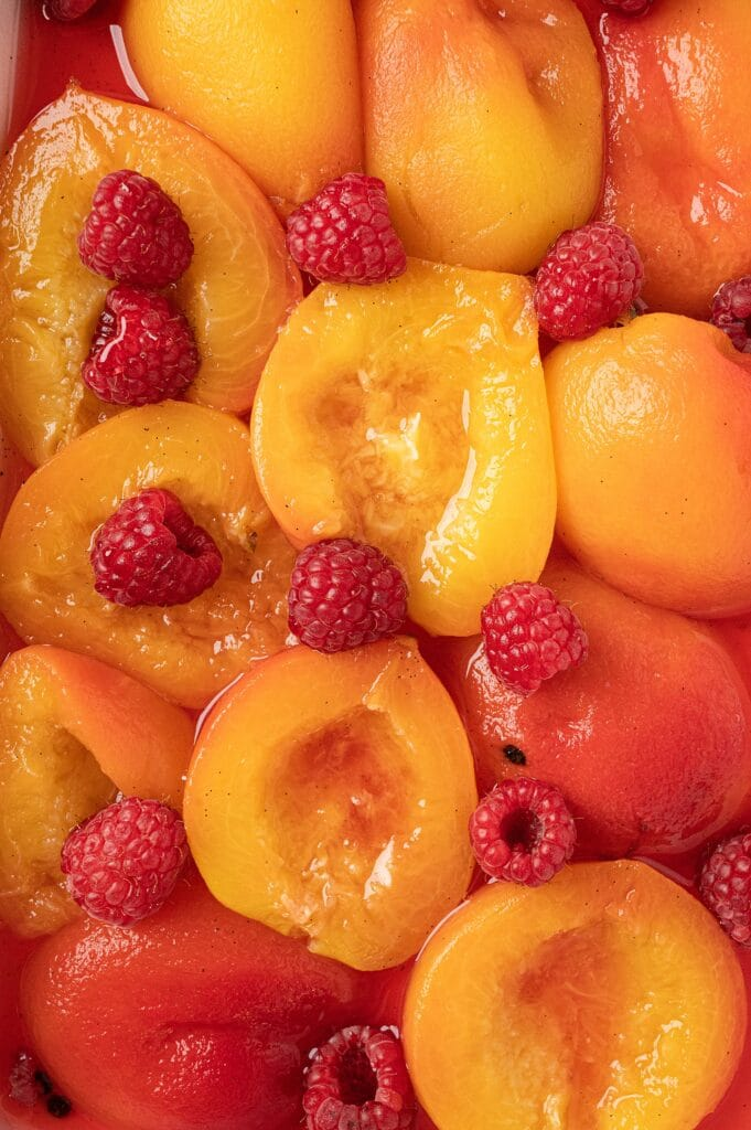 poached peaches with raspberries in a casserole dish
