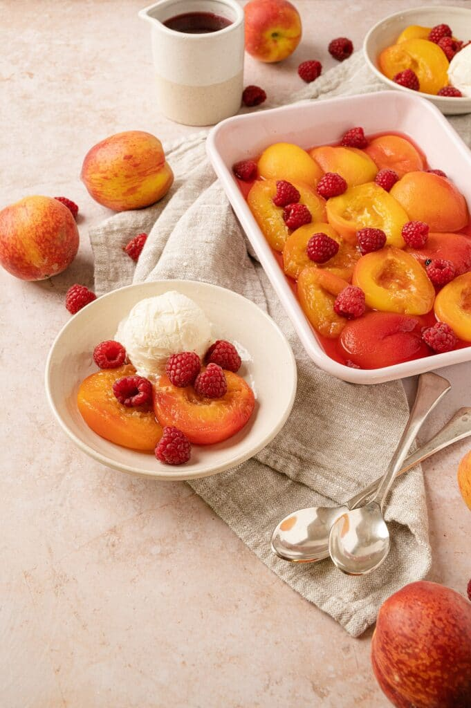 poached peaches with raspberries in a bowl with peaches and casserole dish behind