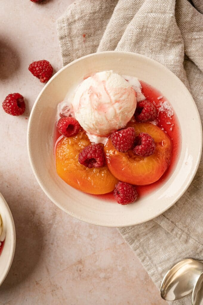 bowl of poached peaches with raspberries