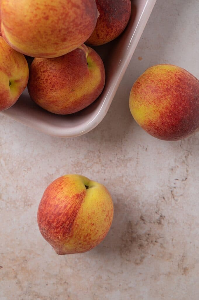 bowl of peaches with two on the table