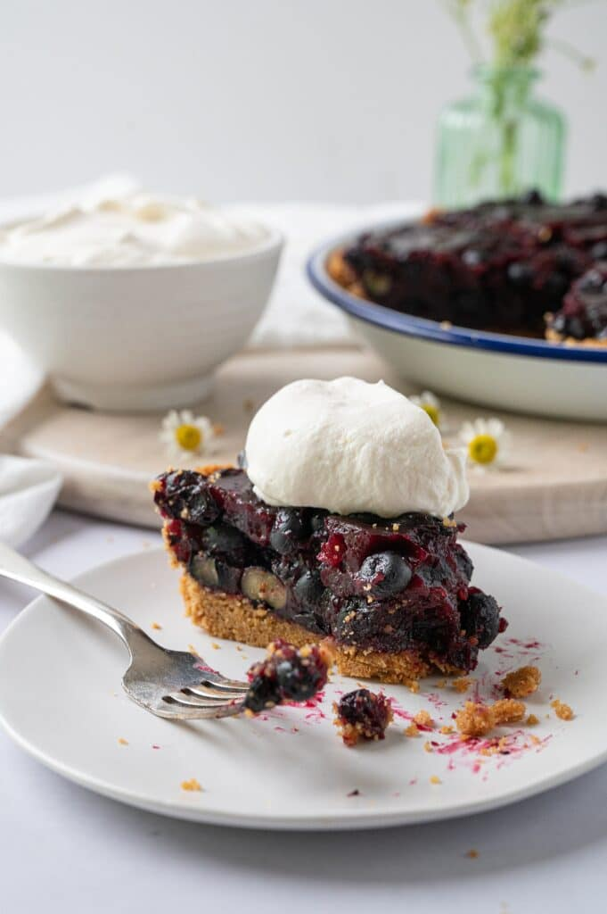 a forkful of blueberry pie on a plate with a slice of pie in the background