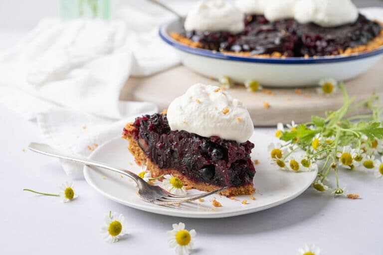 slice of blueberry pie on a plate with whipped cream and the whole pie in the background