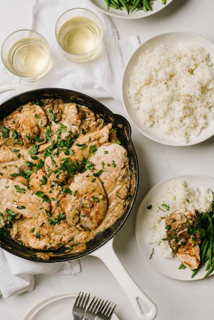 skillet of boursin chicken with glasses of wine and bowl of rice with a plate of chicken with green beans and rice