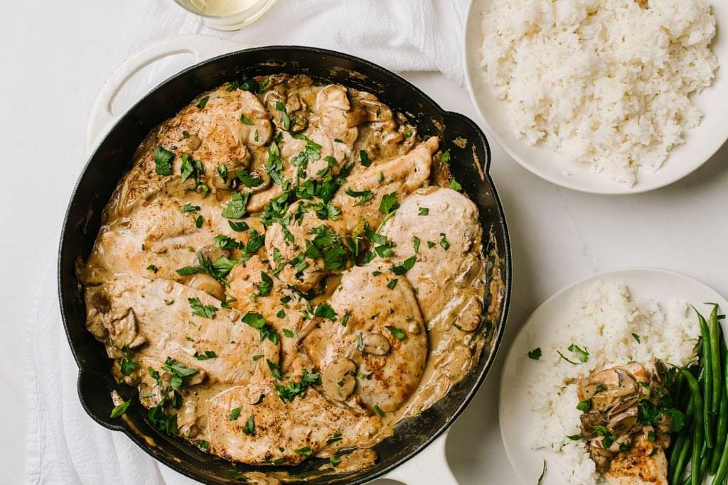 Chicken with Boursin mushroom sauce with rice and green beans on white plate