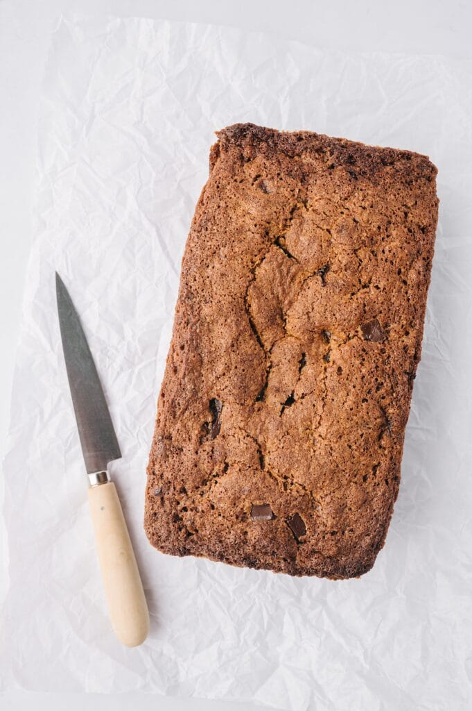 loaf of best banana bread ever on parchment paper with a knive