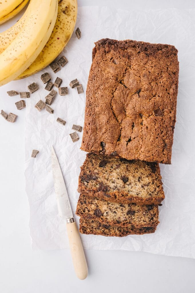 loaf of best banana bread ever sliced with chocolate chunks and bananas