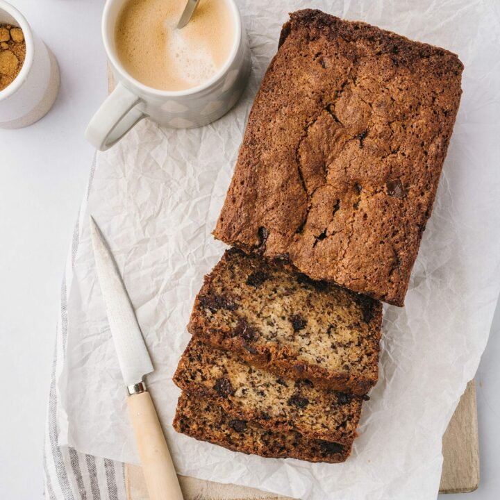 best banana bread ever on parchment paper with a knife and cups of coffee
