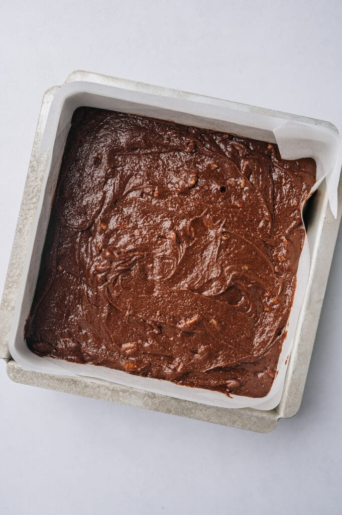 matt's crazy brownies batter in a pan lined with parchment paper ready to be baked