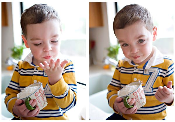 young boy licking powdered sugar off of his fingers.