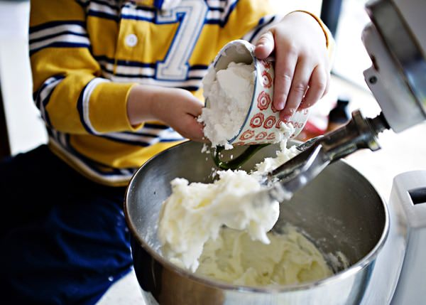 young boy at electric stand mixer, making homemade potato candy