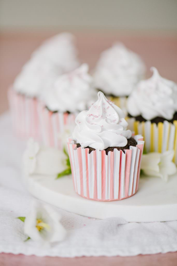 italian meringue boiled icing chocolate cupcakes on a platter with white flowers and pink sugar decorations