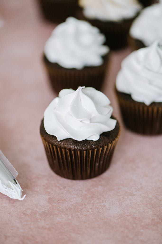chocolate cupcake with piping bag of italian meringue icing in it