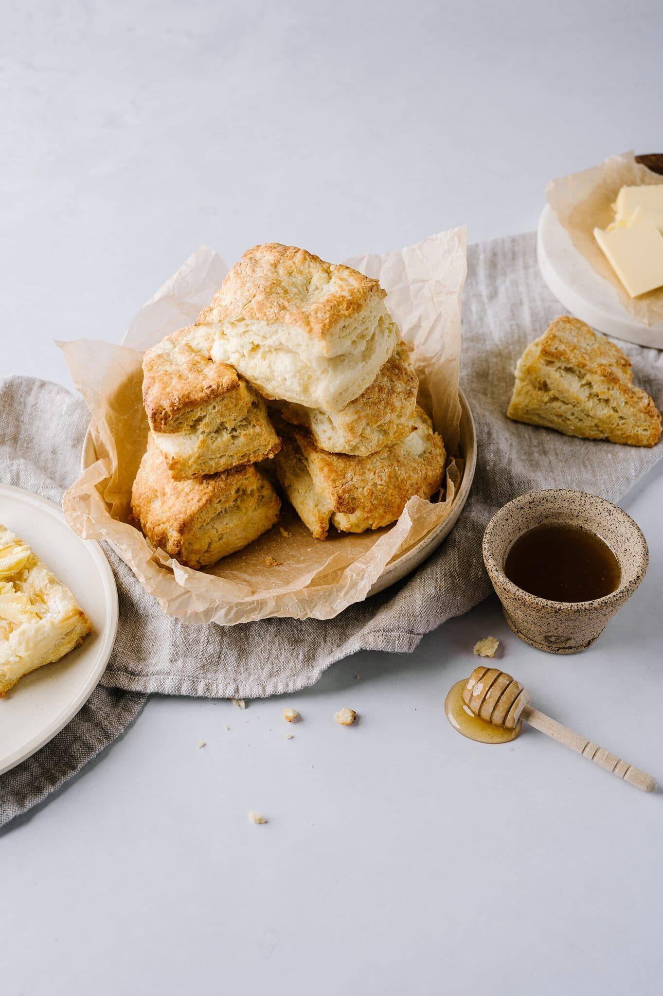 bowl of cream cheese biscuits with a cup of honey