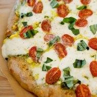 corn pesto tomato pizza