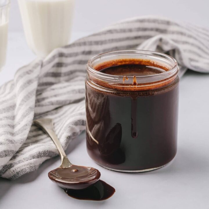 best chocolate sauce in a jar with a spoonful beside it and a glass of milk in the background