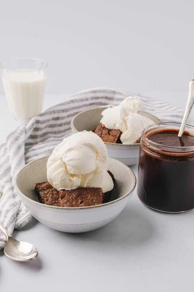 jar of best chocolate sauce with bowls of brownie and ice cream and a glass of milk in the background
