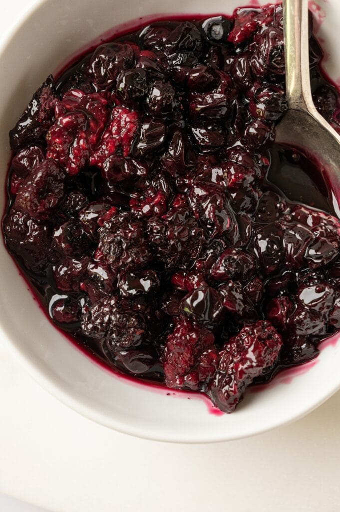 roasted summer berries in a bowl with a spoon