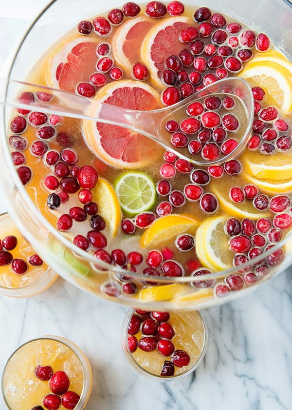 punch bowl filled with holiday citrus sangria garnished with citrus slices and cranberries
