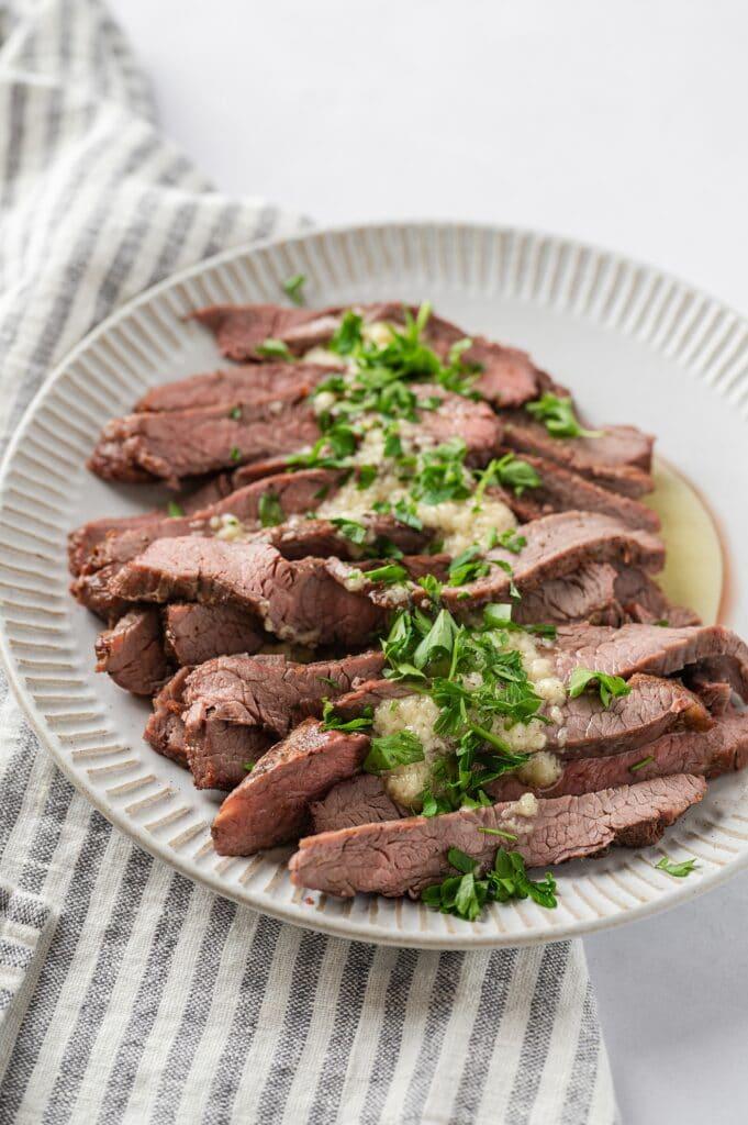 flank steak with garlic butter sauce on a plate