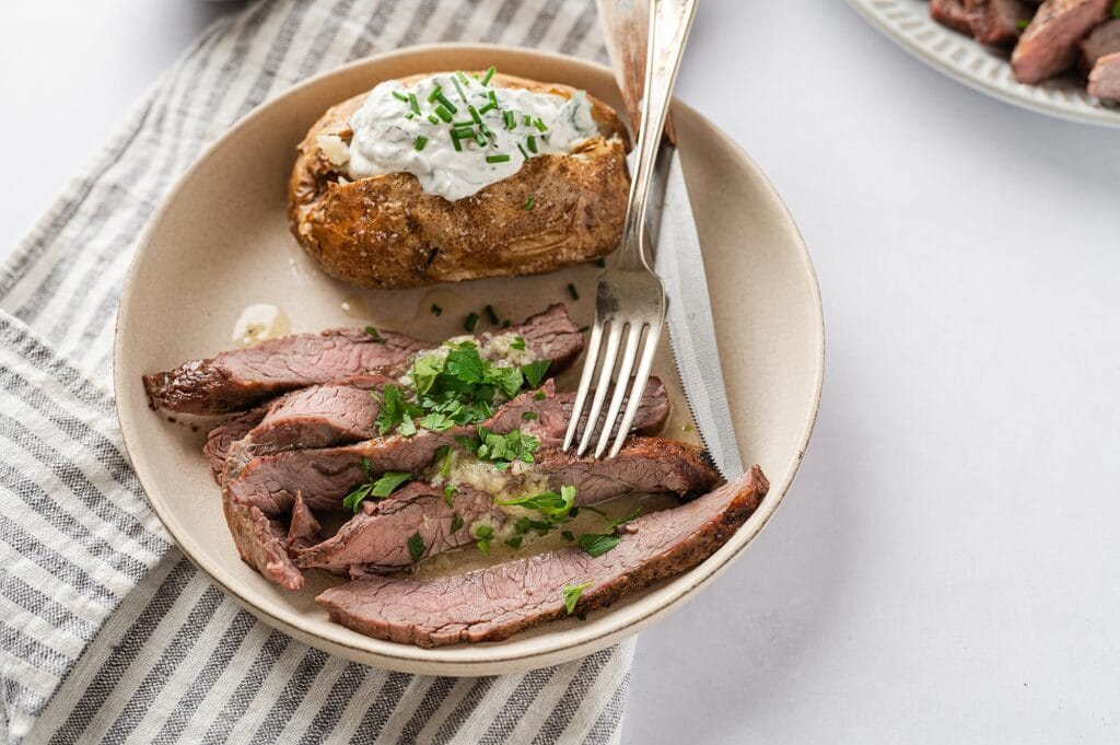 flank steak with garlic butter sauce on a plate with a baked potato with sour cream, chives, a fork and knife