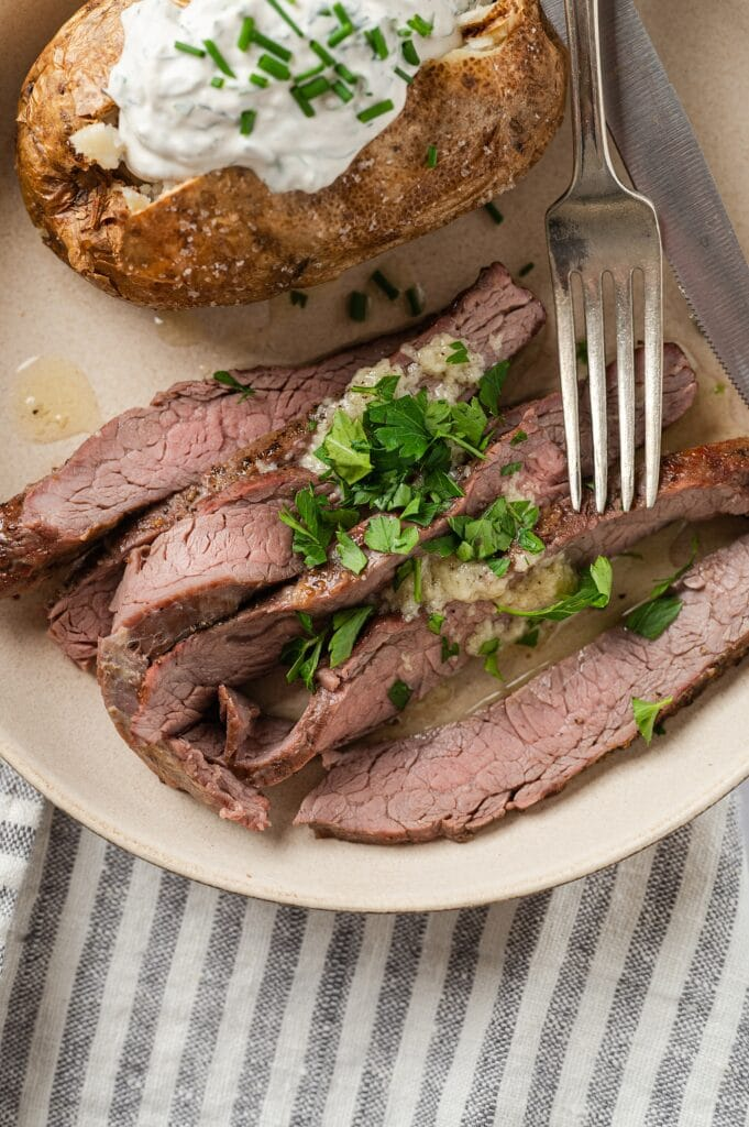 flank steak with garlic butter sauce and a baked potato with sour cream and chives