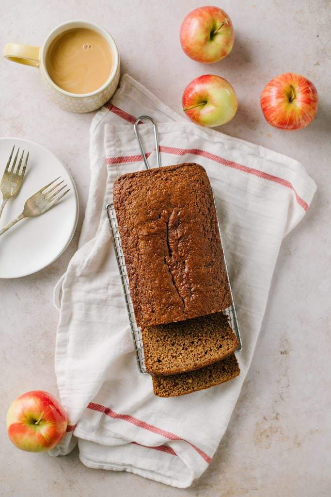 Applesauce Spice Bread on a rack with apples and coffee around it
