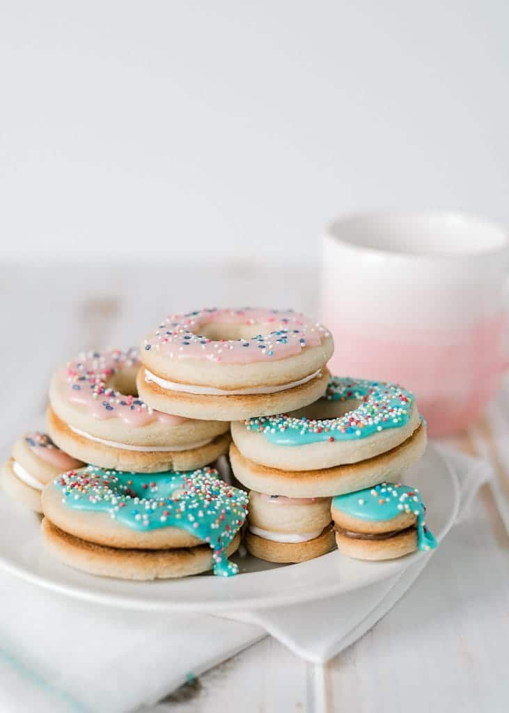 doughnut sandwich cookies on a plate with a coffee cup