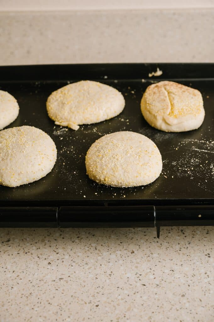 huckleberry english muffin dough on a griddle to be baked