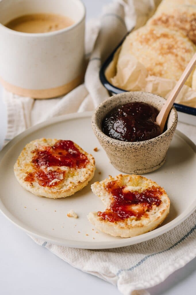 huckleberry english muffins on a plate with jam and dish of muffins and coffee in the background