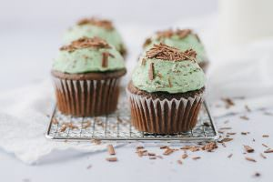 4 mint chocolate chip cupcakes on a rack with chocolate shavings