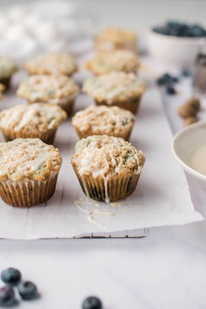 blueberry pancake muffins on a rack with parchment with a bowl of glaze