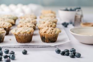 Blueberry muffins with crumb top on a wire rack with a bowl of glaze and blueberries