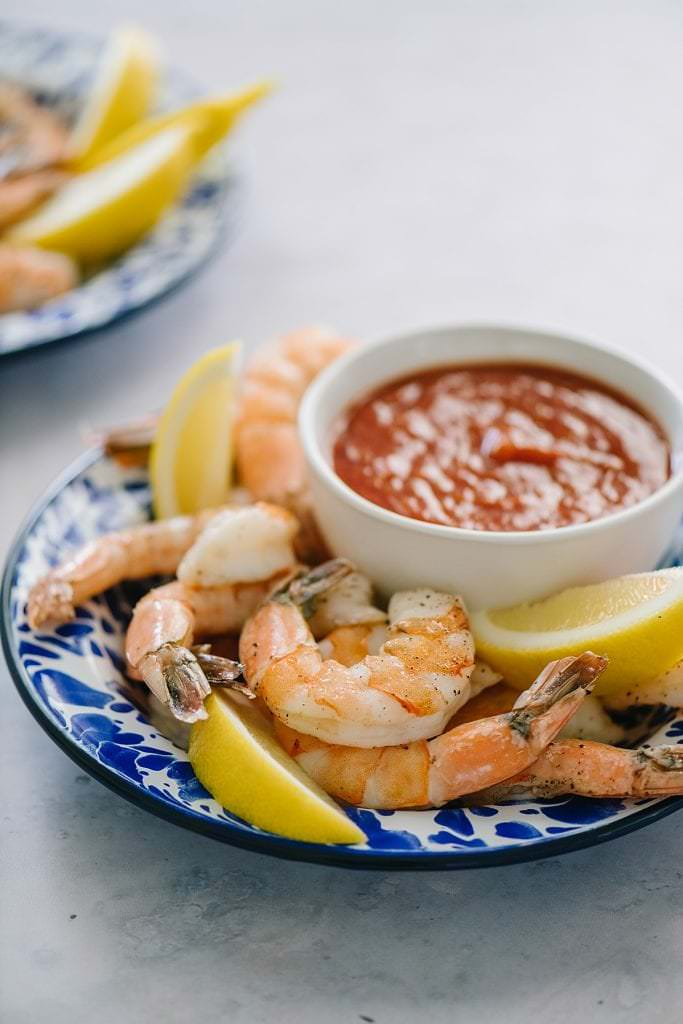 two plates with roasted shrimp and cocktail sauce