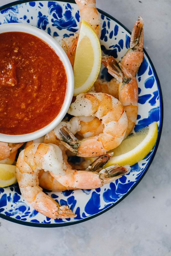 shrimp on a plate with cocktail sauce and lemons.