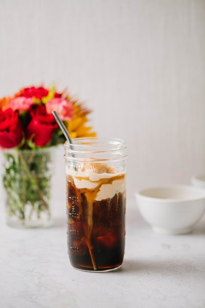 Iced Coffee with a vase of flowers and white bowls of cream