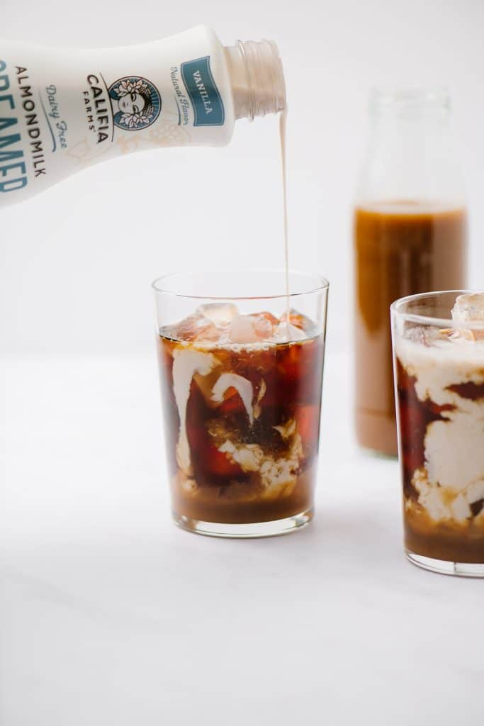 cream pouring into an iced coffee