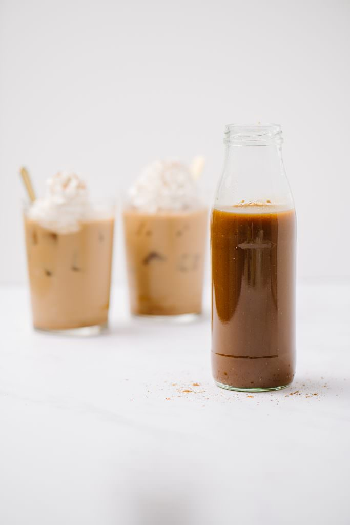 Dairy-Free Pumpkin Spice Syrup in a jar with two iced coffees in background.