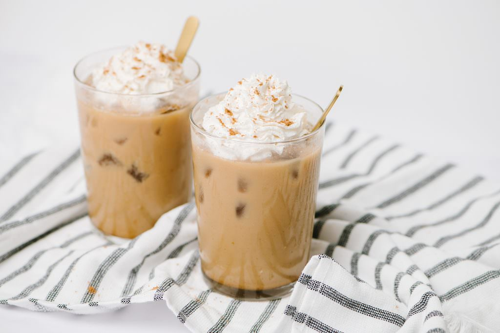 Two Ice Pumpkin Spice Coffee in a glass with gold spoons.