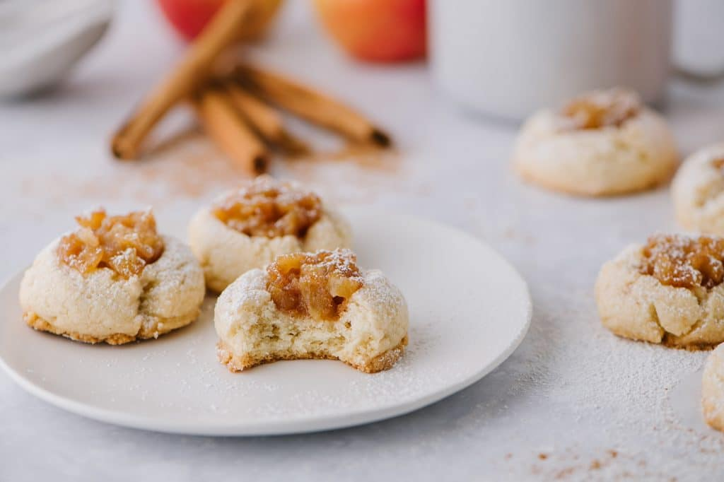 apple pie cookies on a plate with apples and cinnamon in the background
