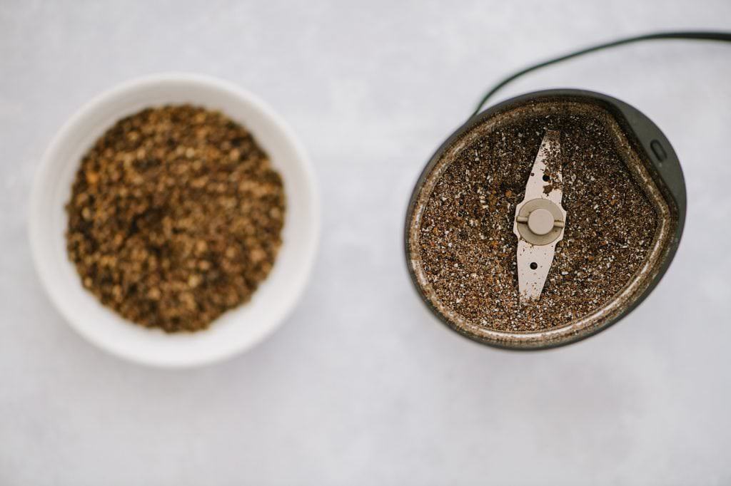 grinding cardamom in a coffee grinder