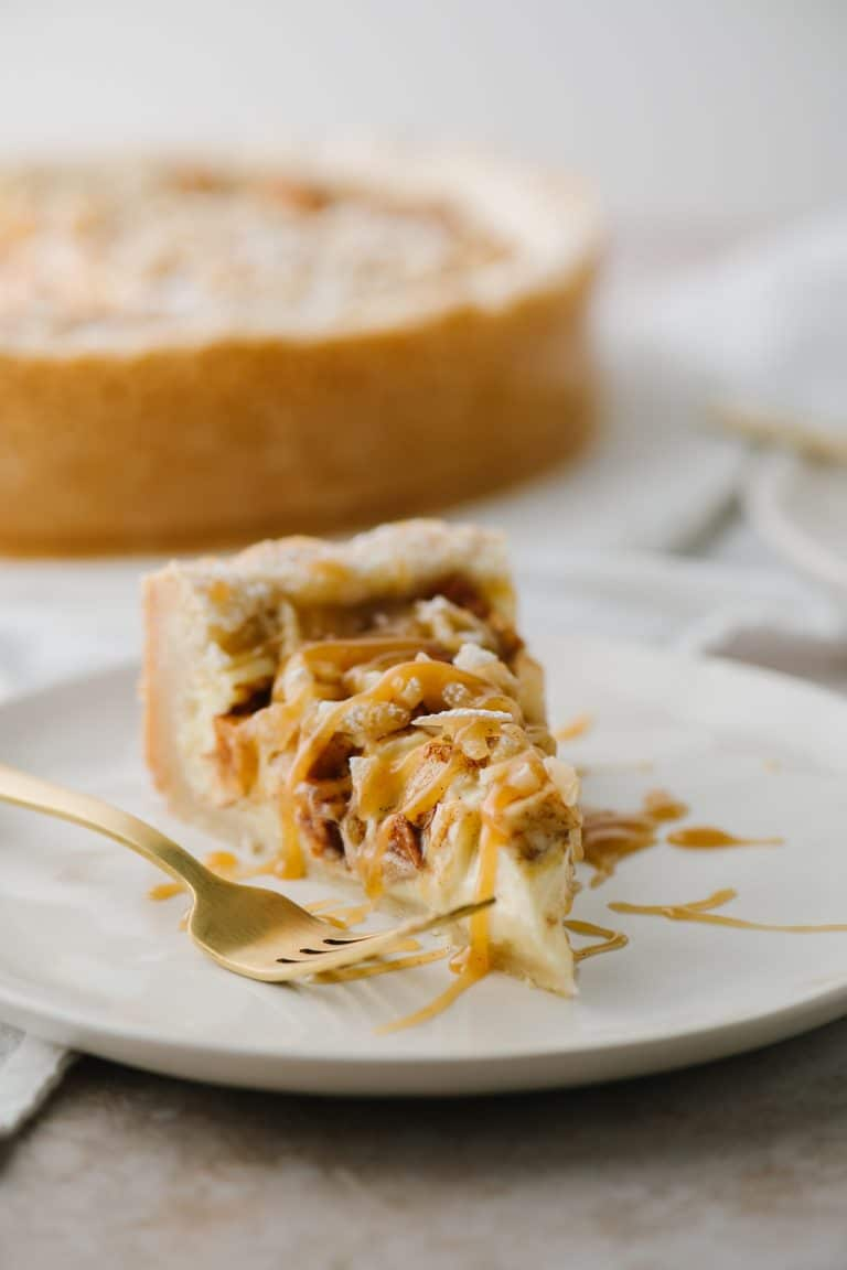slice of apple almond bavarian cheesecake on a plate with a gold fork