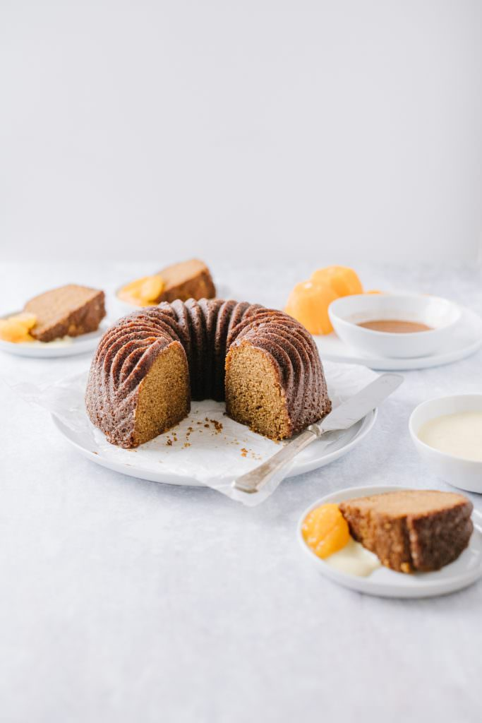 orange gingerbread bundt cake on a plate with slices around it