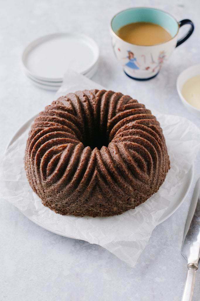 orange gingerbread bundt cake on a plate with a cup of coffee and a bowl of custard