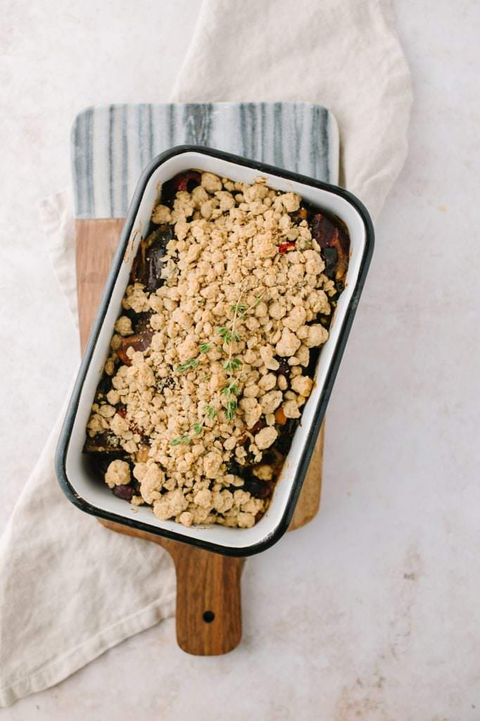 roasted vegetable crisp in a pan with a bowl and spoon