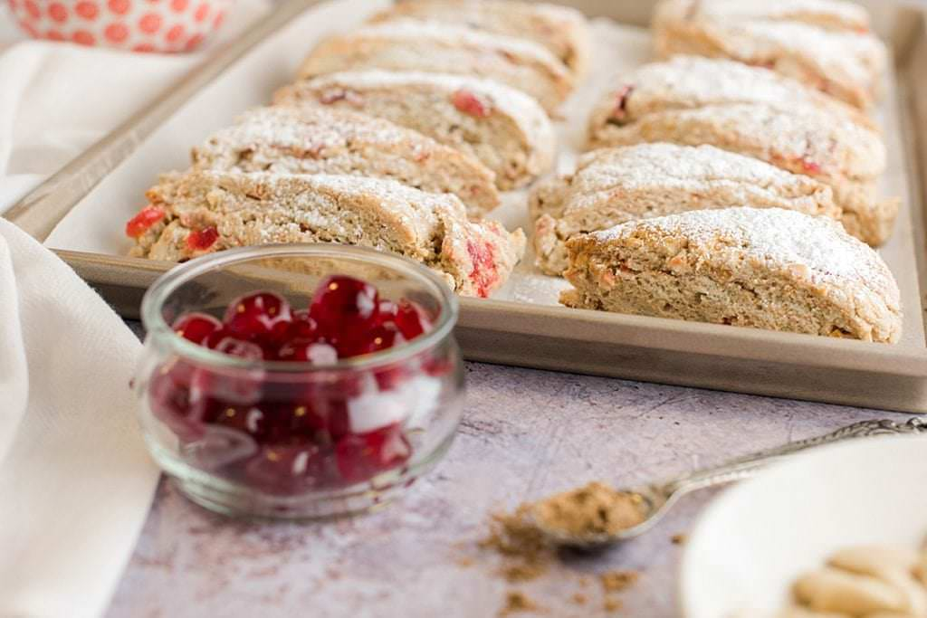 christmas stollen scones on a baking sheet with a bowl of glace cherries