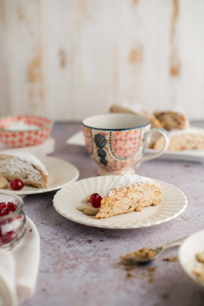 scone on a plate with cherries and almonds