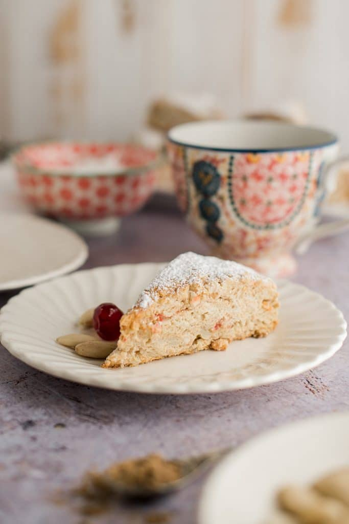 scone on a plate with coffee cup behind it